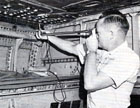 Inspecting the wing pin of a grounded B-47 bomber, circa 1958.